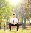 Relaxed businessman sitting on bench in a park on sunny day