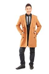 Full length portrait of a smiling handsome man wearing coat