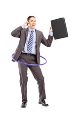 Young businessman dancing with hula hoop talking on phone