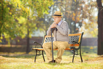 Sad senior man with cane sitting on a wooden bench in a park