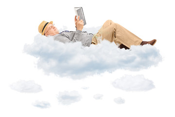 Senior man reading a book and lying on clouds