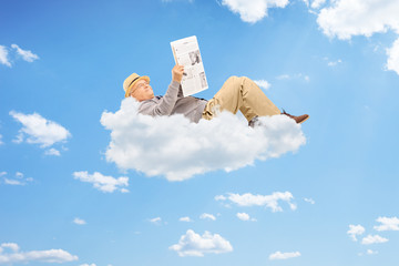 Senior man reading newspaper and lying on clouds