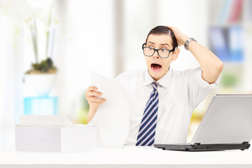 Shocked young accountant in the office looking at expensive bill