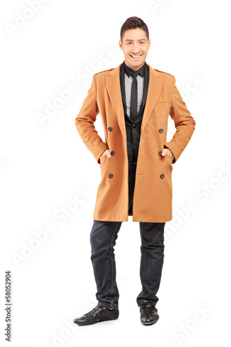 Full length portrait of a smiling handsome man wearing coat