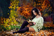Young caucasian sensual woman reading a book in romantic autumn