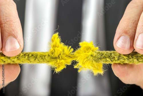 Businessman holding torn rope