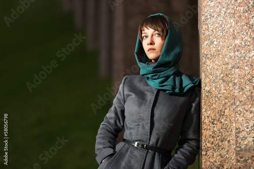 Sad young woman in classic coat at the wall