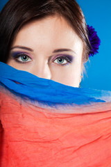 woman hides her face with shawl on blue