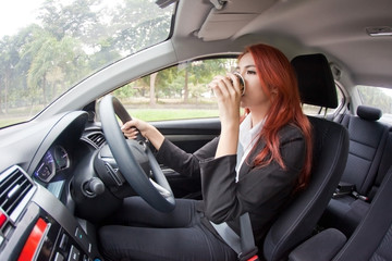 Businesswoman drinking coffee while driving