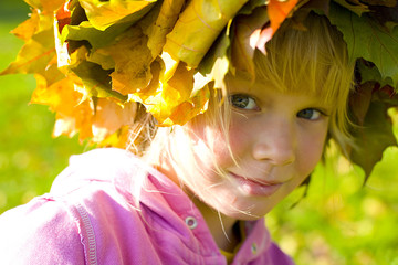 Portrait of a six-year girl in a wreath of autumn leaves close u