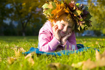 Portrait of the beautiful six-year-old girl in a wreath from aut