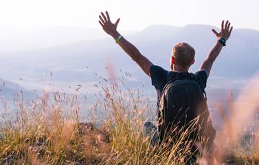 Man greeting sunrise on the mountain