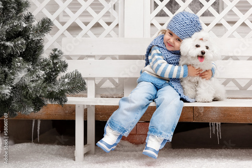 Girl with a dog on a bench outside the house