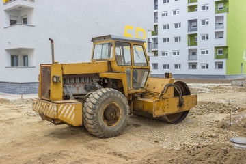 Yellow road roller in the new residential area