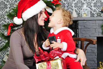 little boy near the tree with her mother in a Santa suit