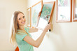 Happy beautiful woman hanging  pictures