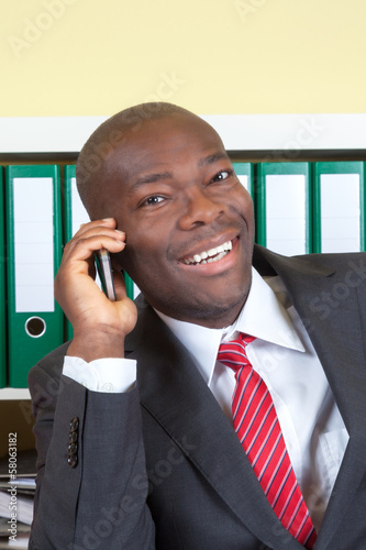 African businessman laughing at phone