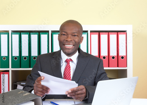 Laughing african businessman reading a letter