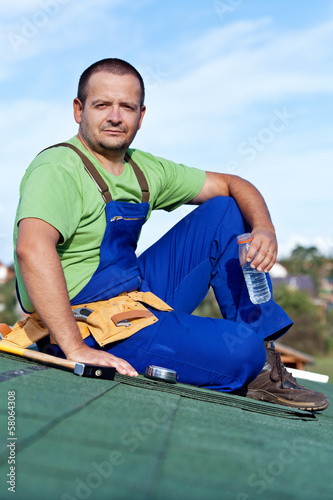 Worker laying bitumen roof shingles