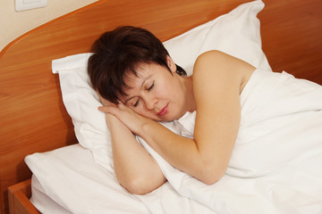 Woman soundly sleeping on a bed