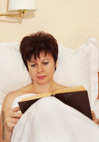 Woman reads a book before sleeping