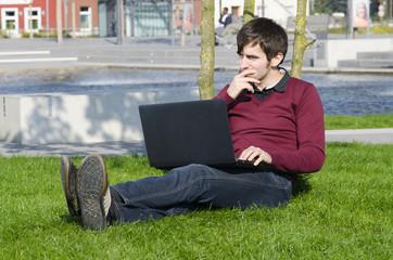 nachdenklicher mann im park mit laptop