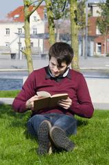 junger mann liest draußen