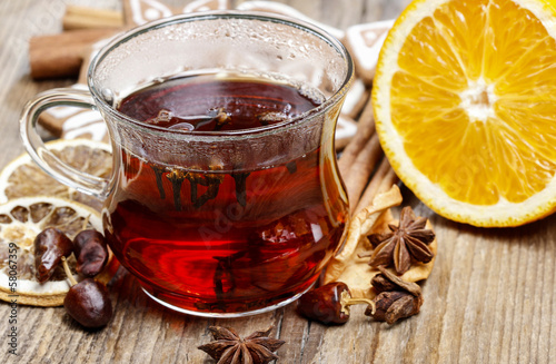 Glass of hot steaming tea among christmas decorations on wooden