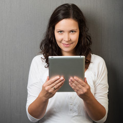 lächelnde frau schaut über tablet-pc