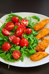 chicken nuggets served with ruccola and cherry tomato