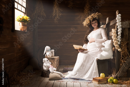 Portrait of a young pregnant woman in a village hut
