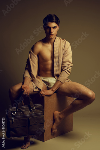 Male fashion concept. Handsome man in uderwear with leather bag