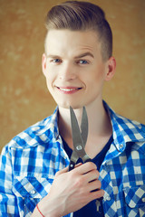 Hipster with very handsome face smiling & holding scissors