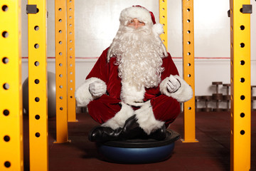 Santa Claus sitting in yoga position in gym