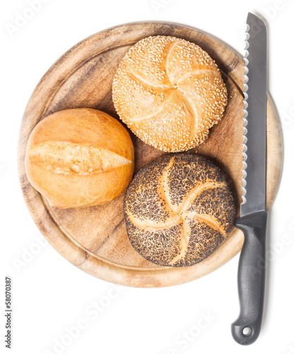 Different bread rolls on cutting board with knife