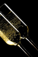 a pair of tilted flutes of champagne with golden bubbles