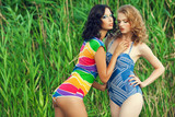 Two gorgeous young women (girlfriends) in trendy swimsuits
