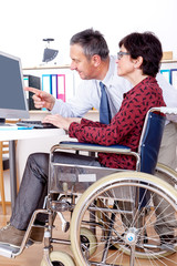 Man helps a wheelchair user in the office