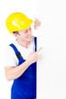 junger Bauarbeiter weist auf Werbetafel