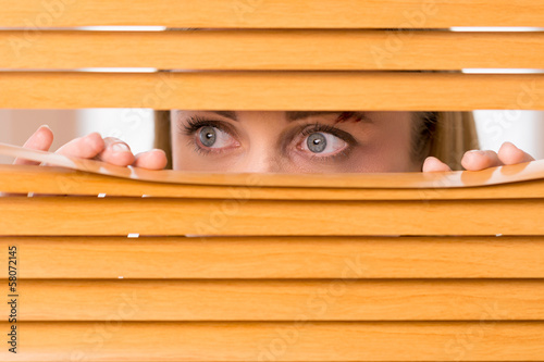 Close up of female eyes looking outside from blinds.