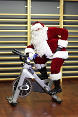 active Santa Claus break in  training on exercise bike