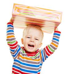 Jubelndes Kind zu Weihnachten mit Geschenk
