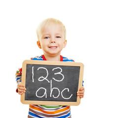 Kind hält Tafel mit Zahlen und Buchstaben
