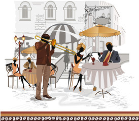 Street cafes with a musician and people drinking coffee