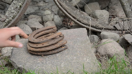 Stack of retro horse shoes on stone and hand take off them