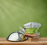 food tray, cap chef and cookbook on a green vintage background
