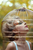 Beautiful blonde girl in a golden cage