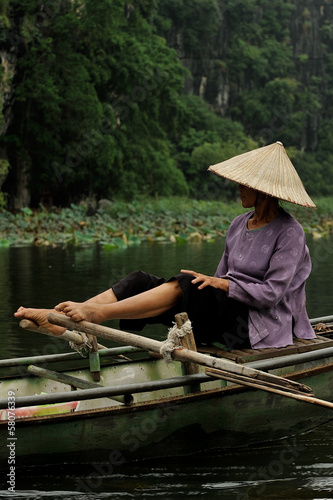 Vietnamese girl driving a boat with his feet