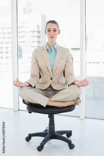 Focused chic businesswoman sitting in lotus position on her swiv