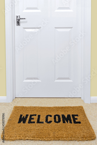 Welcome doormat outside a door.